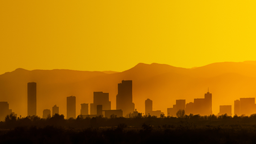 A bright and hazy orange sunset silhouettes the Denver, Colorado skyline against the Foothills of the Rocky Mountains.
